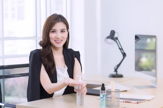 Una bella donna d'ufficio è seduta e preme un gel alcolico per lavarsi felicemente le mani al lavoro