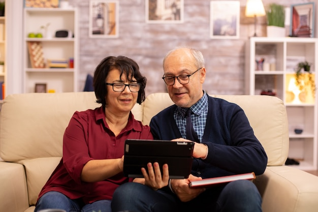 Bella vecchia coppia che utilizza una tavoletta digitale per chattare con la propria famiglia. anziani che utilizzano la tecnologia moderna