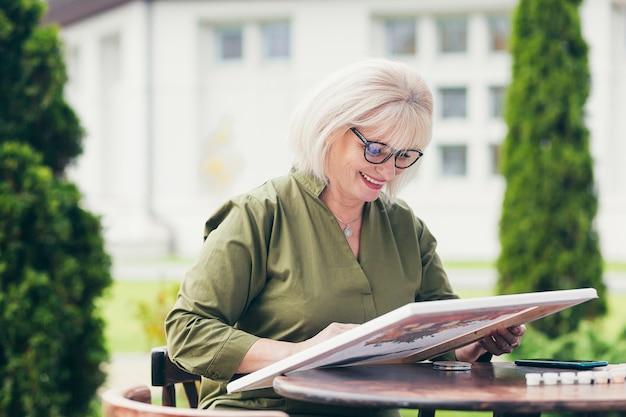 Bella donna anziana che riposa, sorride e dipinge un quadro, dipinge su tela, artista