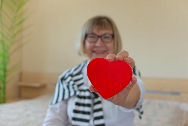 Bella donna anziana contro con un cuore nelle sue mani della sua camera da letto a casa giornata dei cittadini anziani