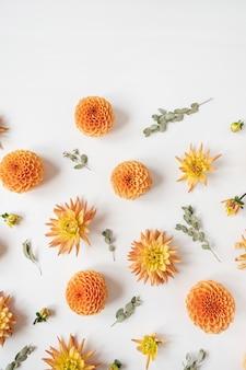 Bellissimi boccioli di fiori dalia arancione e rami di eucalipto