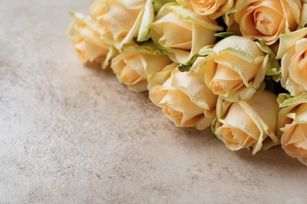 Belle rose arancioni su uno sfondo di cemento chiaro. composizione diagonale
