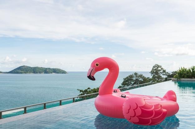 Bella piscina all'aperto nel resort dell'hotel con il fenicottero galleggiante intorno alla nuvola bianca dell'oceano del mare su cielo blu per il concetto di viaggio di vacanza di vacanza