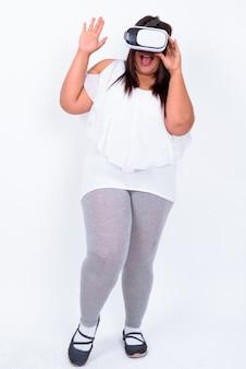 Bella donna asiatica in sovrappeso contro il muro bianco