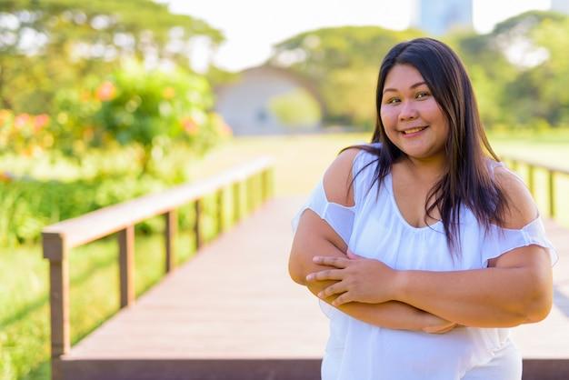 Bella donna asiatica di peso eccessivo che si rilassa al parco