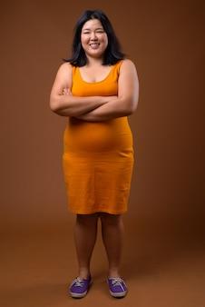 Bella donna asiatica sovrappeso che indossa un abito senza maniche arancione