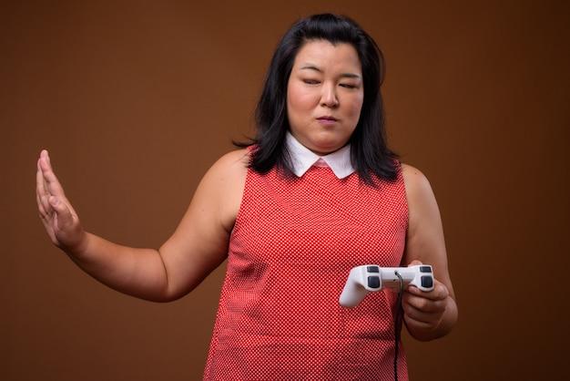 Bella donna asiatica in sovrappeso che indossa un abito rosso