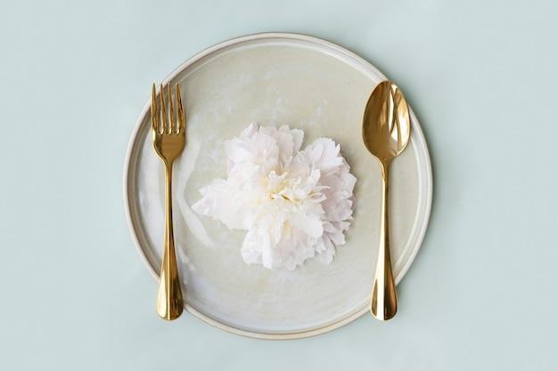 Bella tavola da neve paeonia su un piatto con cucchiaio e forchetta d'oro