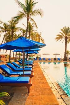 Bella palma con piscina sedia ombrellone in resort hotel di lusso all'alba - concetto di vacanza e vacanza
