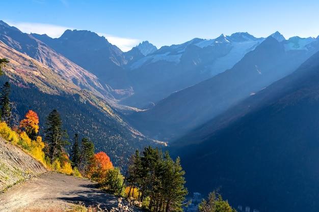 Bellissimo panorama di alte montagne rocciose con cime innevate, possenti ghiacciai e luminosi boschi autunnali nei colori giallo e arancio al tramonto