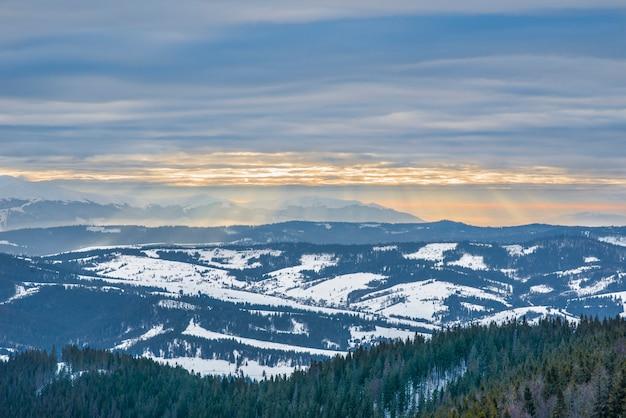 Bellissimo panorama di pendii montani con sentieri che si affacciano sulle colline e boschi di conifere coperto e gelido in una sera d'inverno