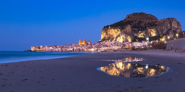 Bella vista panoramica della spiaggia, della cattedrale di cefalù e della città vecchia della città costiera di cefalù durante l'ora blu serale, sicilia, italia