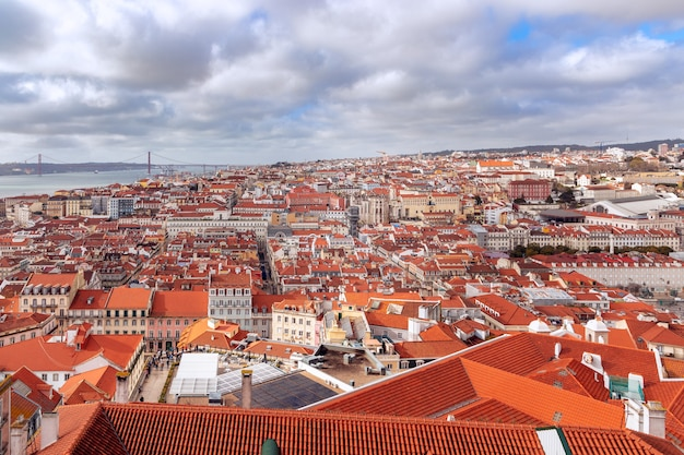 Bella vista panoramica della città di lisbona con tetti di tegole rosse sotto un cielo nuvoloso.