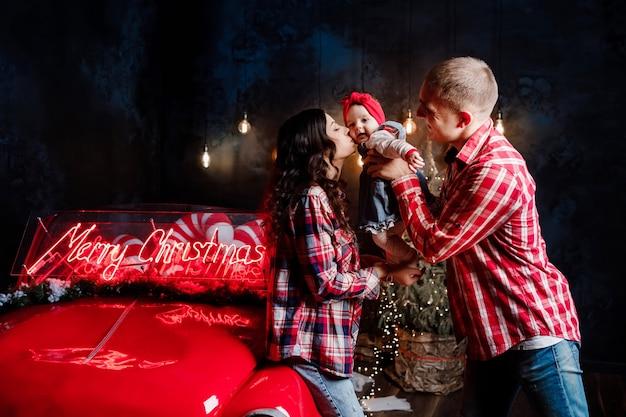 Bei genitori che tengono la loro piccola figlia carina tra le braccia divertendosi vicino auto retrò in studio. scenario di capodanno.