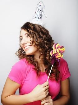 Bellissima modella da festa con lecca-lecca, con cappello di carta su sfondo bianco white