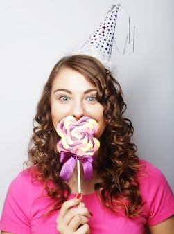 Bellissimo modello di donna da festa con lecca-lecca su sfondo bianco Foto Premium