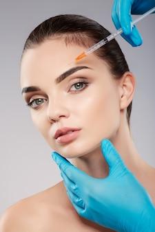 Bella paziente con trucco nudo al fondo dello studio, mani del medico che indossano guanti blu vicino al viso del paziente, che tiene la siringa con botex vicino al viso, guardando la fotocamera.