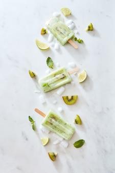 Un bellissimo modello di gelato sano fatto in casa su un bastoncino con fette di ghiaccio, kiwi, lime e foglie di menta su uno sfondo di marmo grigio con spazio per il testo. lay piatto