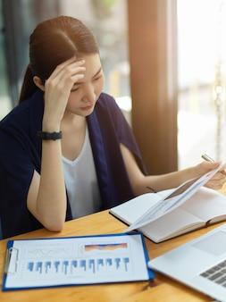 Bella giovane donna d'affari pensierosa che guarda il rapporto di vendita aziendale in ufficio, lavora con la pressione, pensa e risolve i problemi aziendali