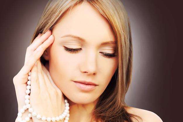 Bella ragazza perfetta con gioielli di perle