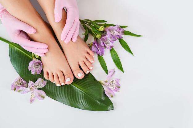 Vista superiore dei piedi femminili delle gambe della bella pelle perfetta con i fiori tropicali e la foglia di palma verde