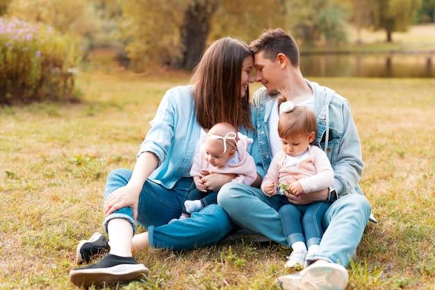 Bella foto di giovani genitori felici che abbracciano i loro bambini piccoli all'aperto nel parco