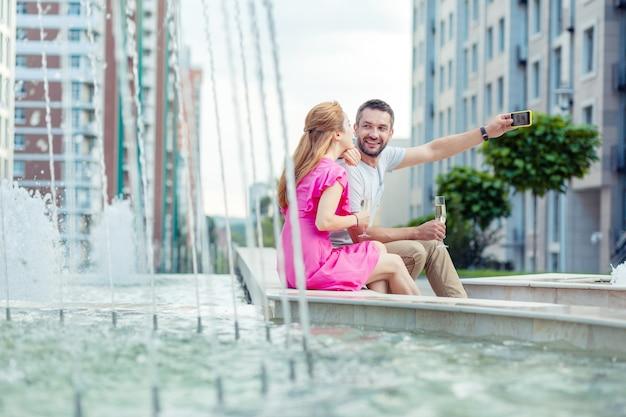 Bella foto. bel uomo positivo seduto insieme alla sua ragazza mentre si fa un selfie con lei