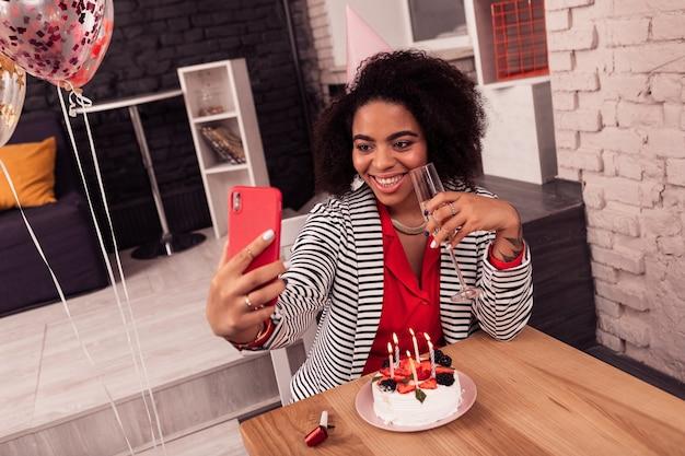 Bella foto. donna attraente positiva che prende un selfie mentre era seduto con un bicchiere di champagne