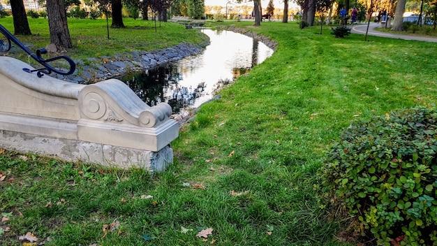 Bella foto del piccolo fiume calmo e del ponte di pietra nel parco aututmn