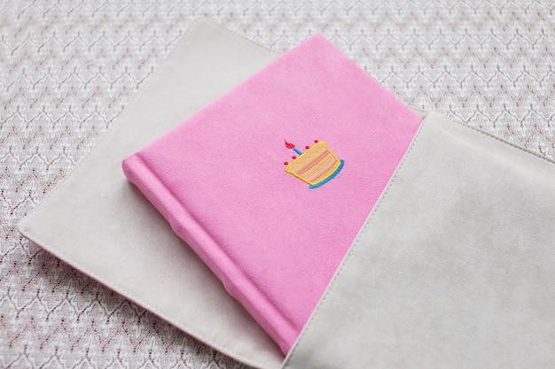 Bellissimo fotolibro con copertina in tessuto rosa chiaro con scatola in tessuto.
