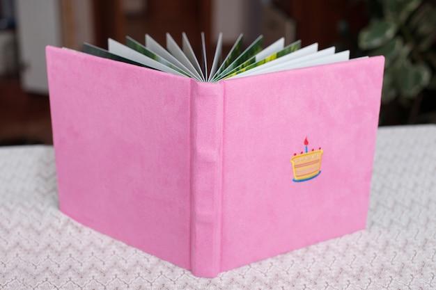 Bellissimo fotolibro con copertina in tessuto rosa chiaro.