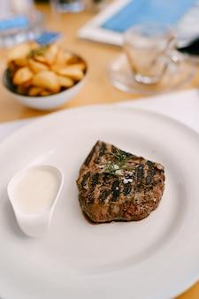 Un bel pezzo di bistecca su un piatto bianco con salsa bianca cosparsa di sale grosso e un rametto
