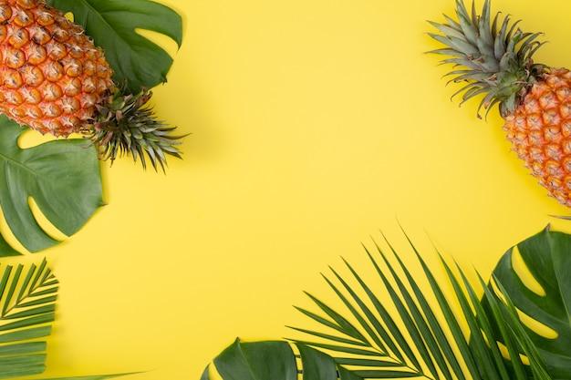 Bellissimo ananas su foglie di monstera di palma tropicale isolato su sfondo giallo pastello brillante, vista dall'alto, piatto, sopra la frutta estiva.