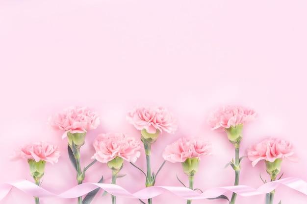 Bellissimo garofano rosa su sfondo rosa pastello da tavolo per il concetto di fiore festa della mamma.