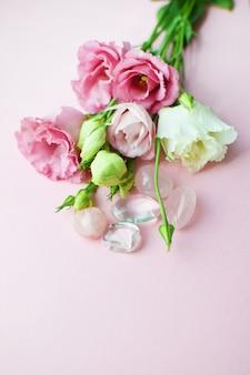 Bellissimi fiori di eustoma rosa (lisianthus) in piena fioritura con quarzo rosa e cristallo di rocca. bouquet di fiori su sfondo rosa