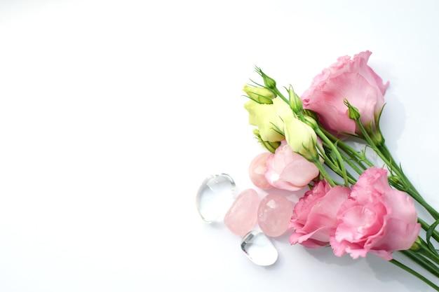 Bellissimi fiori di eustoma rosa (lisianthus) in piena fioritura con quarzo rosa e cristallo di rocca. mazzo di fiori su sfondo bianco