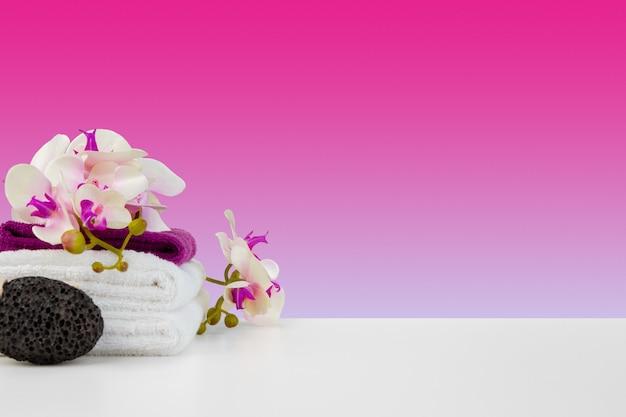 Bellissimi fiori rosa e asciugamani bianchi su sfondo rosa