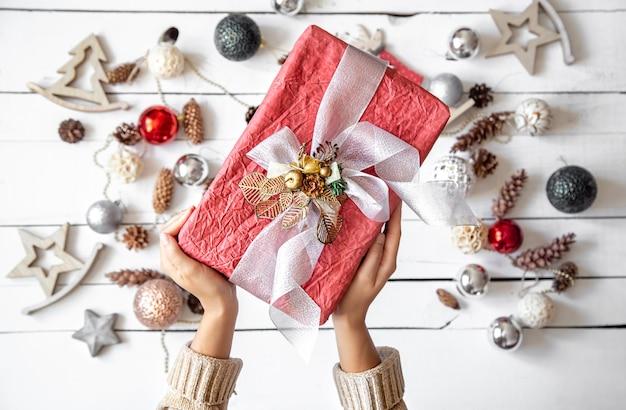 Bella confezione regalo rosa nelle mani contro i dettagli di decorazioni natalizie si chiuda.