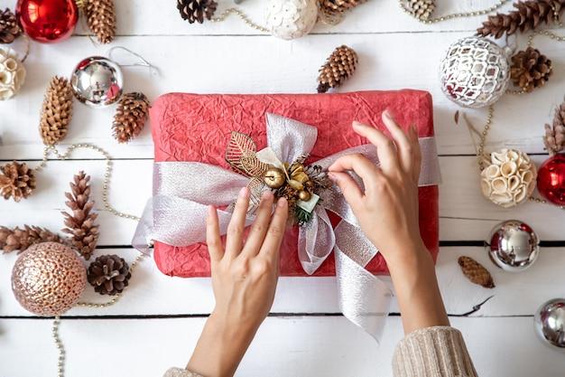Bella confezione regalo rosa nelle mani contro il muro di dettagli di decorazioni natalizie si chiuda.