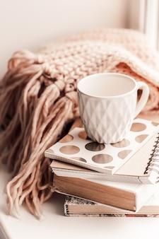 Bella tazza di tè rosa con taccuino e sciarpa lavorata a maglia rosa umore.