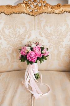 Bellissimo bouquet di peonie rosa con nastri di raso bianco e rosa