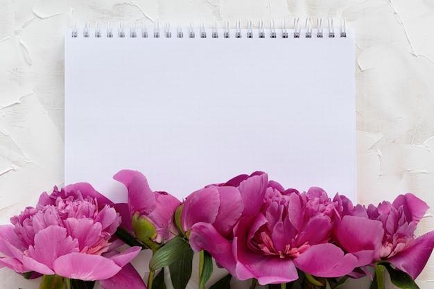 Belle peonie rosa e taccuino bianco. cartolina di vacanza. concetto di vacanza, 8 marzo, festa della mamma. vista dall'alto, luogo per il testo.