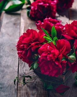 Di un bel colore rosa rosso marsala peonia fiori su tavola in legno rustico con copia spazio per il testo vista dall'alto e stile piatto laici