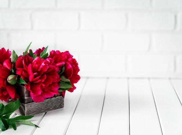 Di un bel colore rosa rosso marsala peonia fiori in una scatola di legno su tavola in legno rustico con copia spazio per il testo.