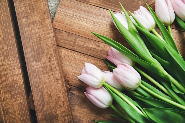 Bei fiori rosa del tulipano sulla tavola di legno