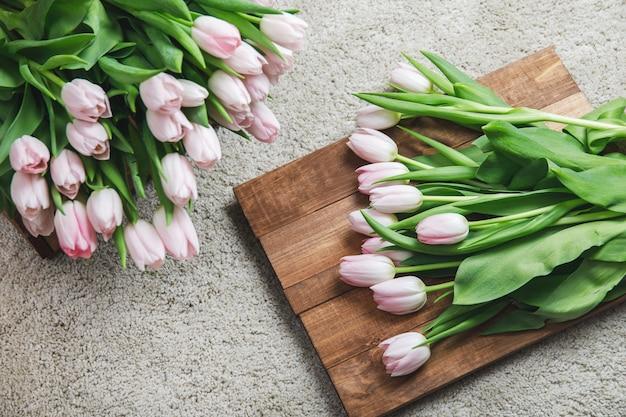 Bei fiori rosa del tulipano nella scatola di legno