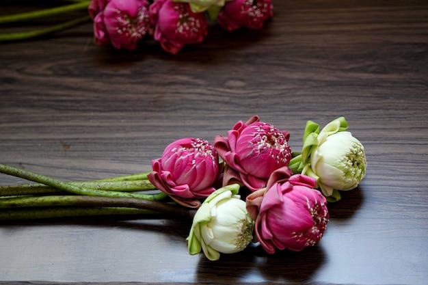 Bellissimo fiore di loto rosa e bianco per pregare buddha su fondo in legno