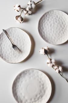 Bellissimi piatti su uno sfondo bianco con cotone. bellissimo layout