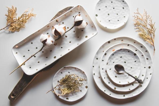 Bellissimi piatti su uno sfondo bianco con pianta essiccata. bellissimo layout