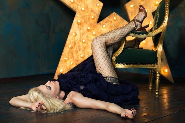 Bella donna bionda adulta giocosa che indossa gonna di pizzo blu scuro e calze a rete in posa sopra la stella luminosa. attrice che suona sul palco. teatro o ballerino.